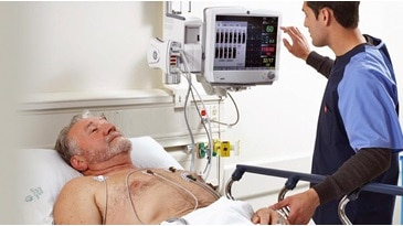 Male clinician addressing alarms from a GE Healthcare Patient Monitoring screen