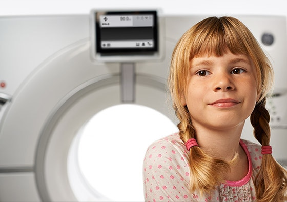 Young girl sitting on Revolution CT machine